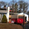 Old painted block chimney being torn down and loaded into dump trailer